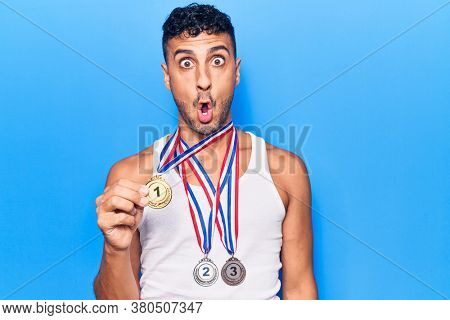 Young hispanic man wearing winner medals scared and amazed with open mouth for surprise, disbelief face
