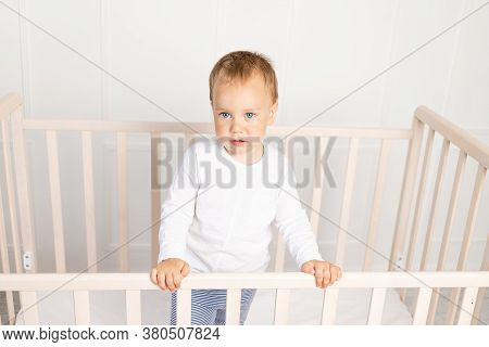 Small Baby Boy 2 Years Old In The Crib Looking At The Camera In The Bright Children's Room, The Chil