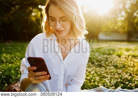 Young woman close-up in white shirt reads message to mobile phone, against green of summer park