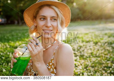 young hipster woman in summer dress and hat with summer accessories and cocktail.
