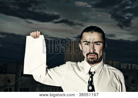 Serious Businessman Holding A Sheet Of Paper