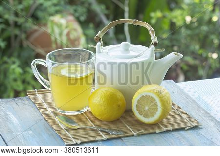Hot Tea Cup With Lemon And Teapot On Garden Background