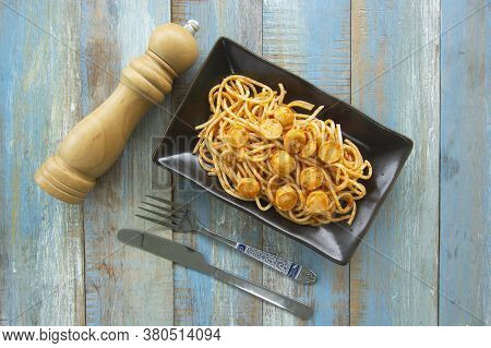 Spaghetti With Fried Sausage In Black Plate On Table