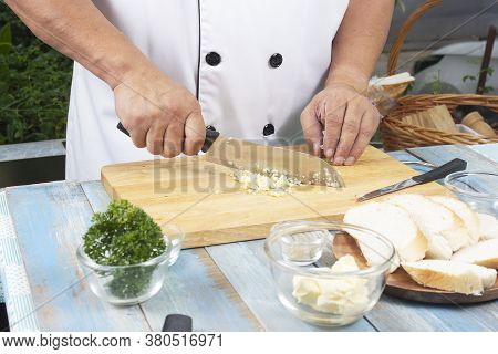 Chef Chopping Garlic For Cooked Garlic Bread / Cooking Garlic Bread Concept