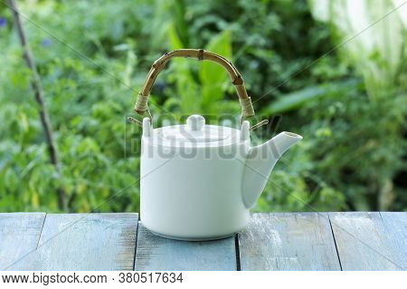 White Teapot On Table Served In Garden
