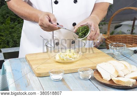 Chef Putting Minced Parsley To Bowl For Cook Garlic Bread / Cooking Garlic Bread Concept
