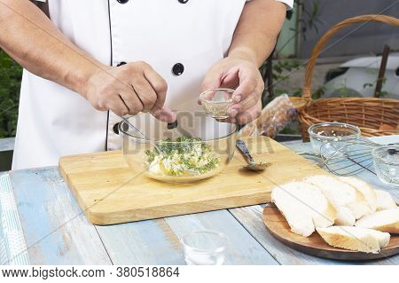 Chef Putting Pepper To Bowl For Cook Garlic Bread / Cooking Garlic Bread Concept