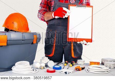 Repairman Worker In Uniform Holding Empty Blank Board.