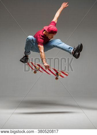 Cool Young Guy Skateboarder Jumps On Skateboard In Studio On Grey Background. Photography About Skat