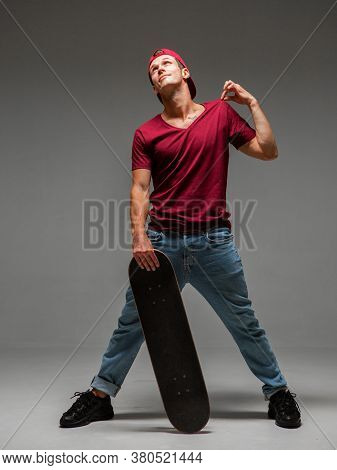 Cool Guy Skateboarder In Baseball Cap Stands With Skateboard In Studio On Grey Background. Photo Abo