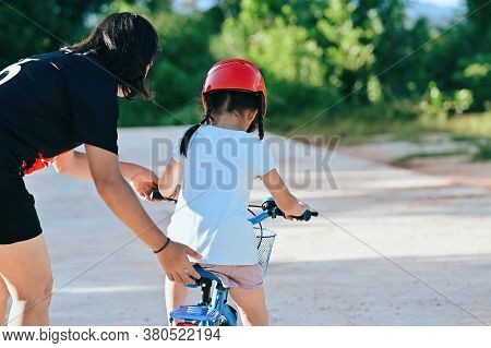 Happy Mother Teaching Little Daughter To Ride A Bicycle. Child Learning To Ride A Bike In The Park A