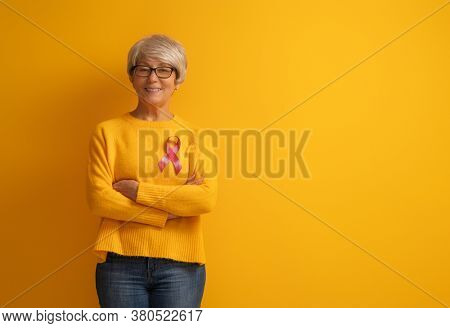 Senior woman on color yellow background. Pink ribbon like a symbol of breast cancer awareness. Support people living with tumor illness.