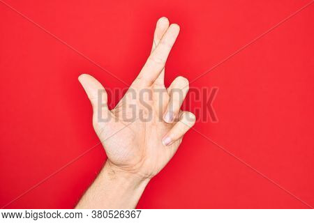 Hand of caucasian young man showing fingers over isolated red background gesturing fingers crossed, superstition and lucky gesture, lucky and hope expression