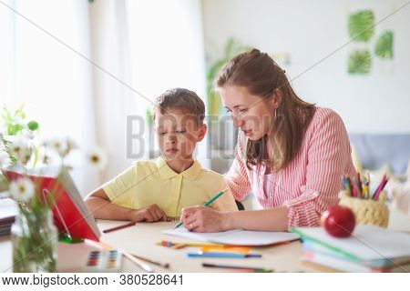 Mother Helps Son To Do Lessons. Correct The Error In Home Lessons. The Tutor Is Engaged With Child,