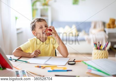 Cheerful carefree boy bites off an Apple sitting at a Desk, after completing school homework. Hungry schoolboy sitting at the desk with book, school supplies, biting the red apple.
