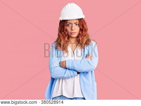 Young latin woman wearing architect hardhat skeptic and nervous, disapproving expression on face with crossed arms. negative person.