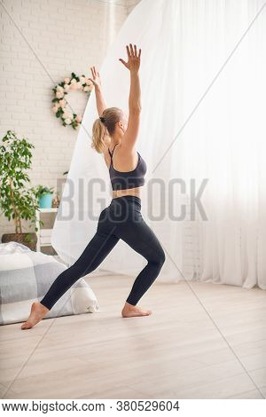 Relaxed Woman Does Sports Exercises In Sportswear At Home. Morning Exercise. Exercises For Hands And