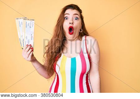 Young redhead woman wearing swimwear holding boarding pass scared and amazed with open mouth for surprise, disbelief face