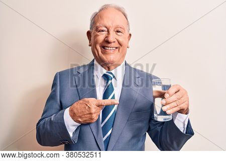 Senior handsome grey-haired businessman wearing suit drinking glass of water to refreshment smiling happy pointing with hand and finger