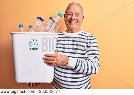 Senior handsome grey-haired man recycling holding wastebasket full of plastic bottles looking positive and happy standing and smiling with a confident smile showing teeth