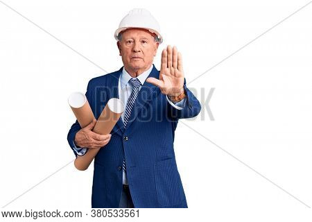 Senior handsome grey-haired man wearing architect hardhat holding blueprints with open hand doing stop sign with serious and confident expression, defense gesture