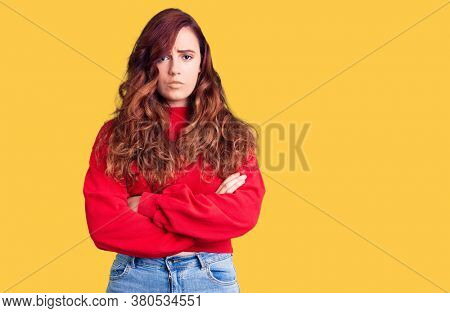 Young beautiful woman wearing casual winter sweater skeptic and nervous, disapproving expression on face with crossed arms. negative person.