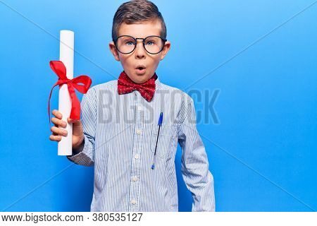 Cute blond kid wearing nerd bow tie and glasses holding diploma scared and amazed with open mouth for surprise, disbelief face