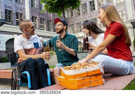Pizza Time. Group Of Friends Taking A Stroll On Citys Street In Summer Day. Handicapped Man With His