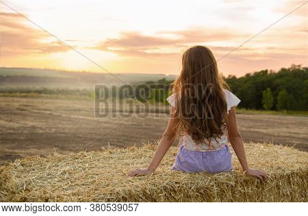 Adorable Little Girl Child Sitting On A Hay Rolls In A Wheat Field At Sunset Back View