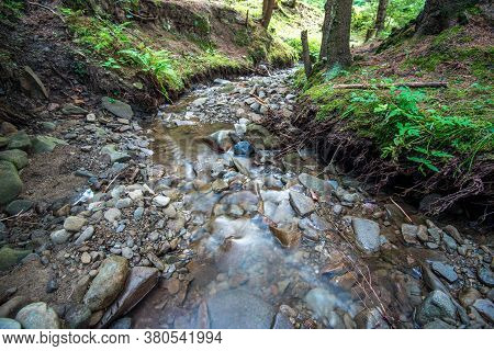 Long Exposure Image Of A Small Mountain Creek, Due The  Heavy Deforestation The Water Is Filled With