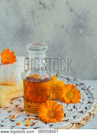 Calendula Products. Bottle Of Cosmetic Or Essential Oil And Fresh Calendula Flowers On Light Backgro