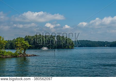 A Houseboat Going By One Of The Islands On The Lake With Other Motorboats In The Background On A Bri
