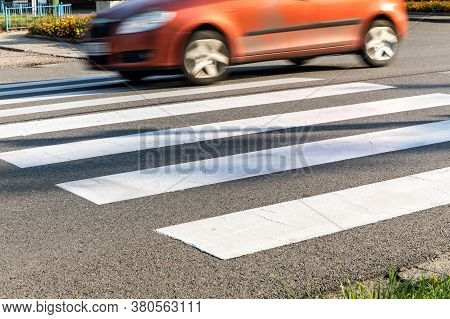 Orange Cars On The Pedestrian Crossing. Pedestrian Crossing Road Marking And Fast Moving Car, Photo