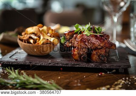 Pork ribs cooked at low temperature. Blackcurrant sauce, parsnip chips with Parmesan cheese. Delicious healthy meat food closeup served on a table for lunch in modern cuisine gourmet restaurant.