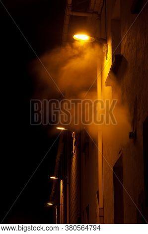Illuminated Street Lights In The Fog At Night.