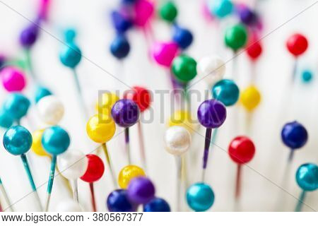 Multicolored Sewing Pins In The White Pin Cushion. Close-up