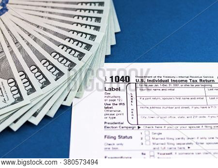 Tax Form 1040 And Dollars On A Blue Table. The Concept Of Business Taxation And Business