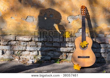 Classical guitar next to old wall