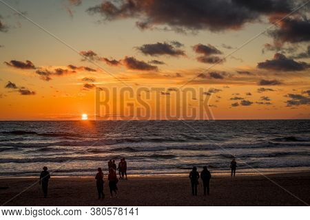 Palanga, Lithuania - July 12, 2020: Sunset In The Baltic Sea With Silhouettes Of People Standing On