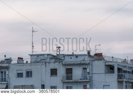 War Air Raid Siren On Residential Buildings Rooftop. Evening View Of Old Mushroom Shaped Attack Warn