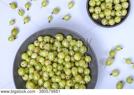 Ripe Green Gooseberry Berry In Plate Bowl. Green Gooseberry On Light Blue Background. Top View