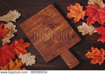 Cutting Board With Autumn Maple, Oak Leaves On Brown Wooden Table. Backgroud For Restaurant Menu . T