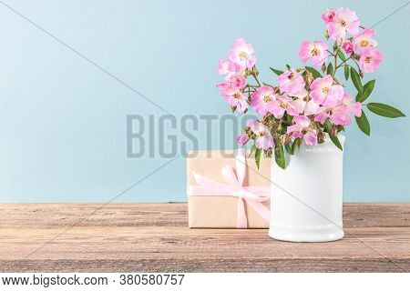 Flowers Composition. Pink Rose Flowers On Vase On Wooden Table. Greeting Card Foe Women Day.