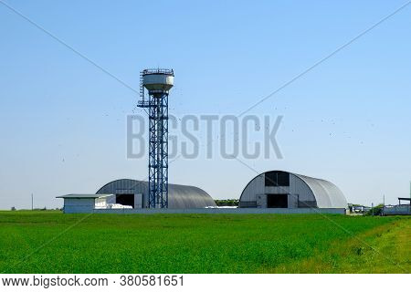 Farm Hangars And Tower. Large Storage For Agricultural Crops. Agribusiness Concept.