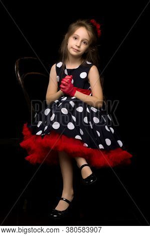 Beautiful Girl Wearing Retro Style Polka Dot Dress Sitting On Chair With Her Hands Clasped, Front Vi