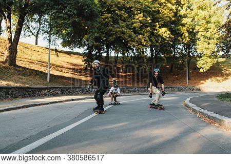 Three Guys Ride A Longboard At Sunset.