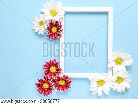 Mockup Square White Frame With White And Red Flowers On Blue Background. View Top. Messege Or Invita