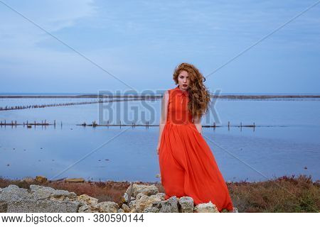 A Young Red-haired Woman With Long Curly Hair In A Red Dress Stands On The Shore Of The Lake. The Cl