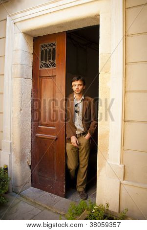Handsome male model leaning on a wooden door