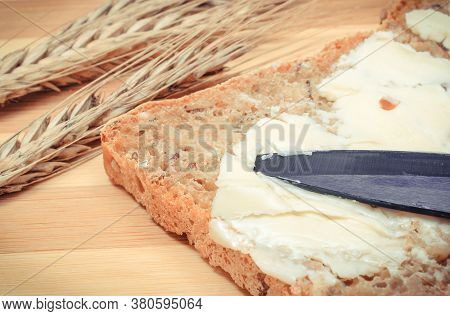 Slice Of Fresh Baked Wholemeal Bread With Butter And Ears Of Wheat